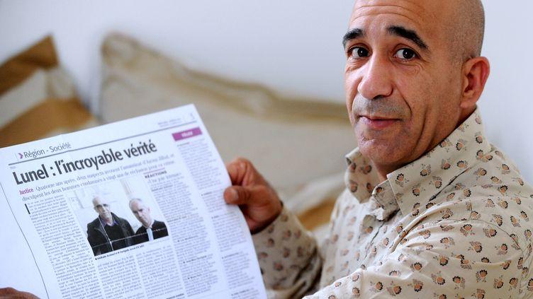 Abderrahim el-Jabri montre un article de presse concernant son procès, le 26 juin 2012 à son domicile d'Ostricourt, dans le Nord. Quelque 900 kilomètres les séparent aujourd'hui mais les destins d'Abdelkader Azzimami et Abderrahim El-Jabri restent liés par l'espoir de voir annuler leur condamnation à 20 ans de prison pour un meurtre qu'ils ont toujours nié. (FRANCOIS LO PRESTI / AFP)