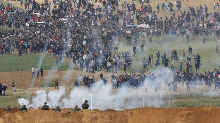 Des soldats israéliens font face à des palestiniens rassemblés à la frontière avec la bande de Gaza, vendredi 30 mars 2018. (JACK GUEZ / AFP)