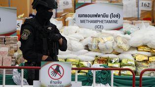 Un policier thaïlandais garde des sacs de méthamphétamines saisis, le 26 juin 2020 à Ayutthaya (Thaïlande). (SOPA IMAGES / CHAIWAT SUBPRASOM / SIPA)