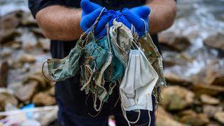 Un homme pose avec des masques jetés qu'il a trouvés sur une plage du quartier résidentiel de Discovery Bay sur l'île périphérique de Lantau à Hong Kong, le 13 mai 2020. (ANTHONY WALLACE / AFP)