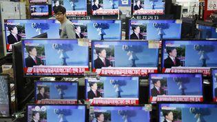 Un vendeur regarde des écrans de télévision retransmettant des images transmises par laCorée du Nord et montrant un possible essai nucléaire, le 6 janvier 2016 à Séoul (Corée du Sud). (KIM HONG-JI / REUTERS)