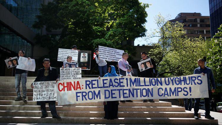 Des personnes brandissent des pancartes pour protester contre le traitement réservé aux Ouïghours par la Chine, à Vancouver (Canada), le 8 mai 2019. (LINDSEY WASSON / REUTERS)