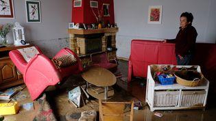 Une habitante de Villegailhenc (Aude)au milieu de son salon dévasté, le 15 octobre 2018, après des inondations. (ERIC CABANIS / AFP)