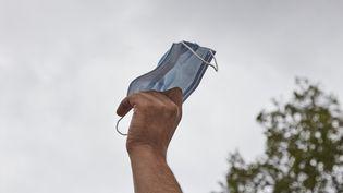 Un masque sanitaire retiré par un militant lors d'une manifestation anti-masques à Paris, le 29 août 2020. (ADNAN FARZAT / NURPHOTO)