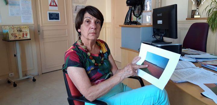 Paulette Deschamps, la maire du Perray en Yvelines avec une photo du champ rouge après l'épandage. (FRANCEINFO / RADIOFRANCE)