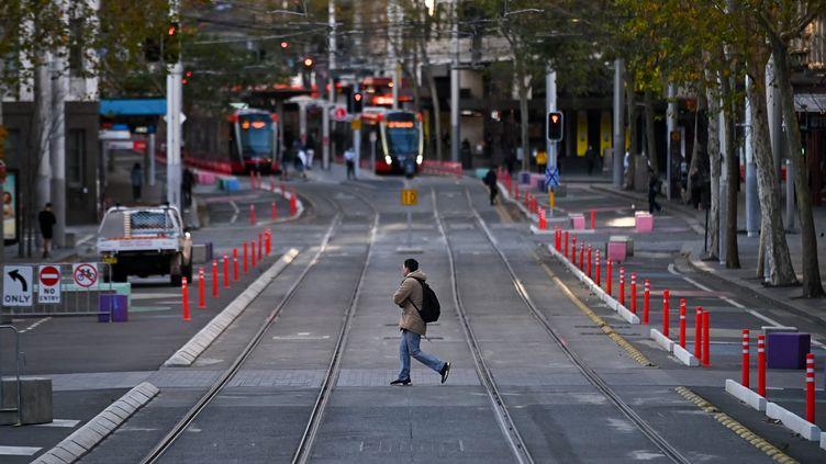 Un homme traverse la rue George à Sydney (Australie), le 26 juin 2021. (STEVEN SAPHORE / ANADOLU AGENCY / AFP)