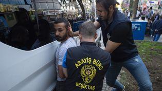 Des policiers turcs arrêtent un Kurde en marge d'une manifestation contre l'opération militaire en Syrie, le 13 octobre 2019 à Istanbul. (YASIN AKGUL / AFP)