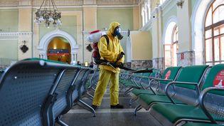 Un employé duministèredes Situations d'urgence désinfecte la gare deRizhskyà Moscou, le 17 juin 2021. (MAKSIM BLINOV / SPUTNIK / AFP)