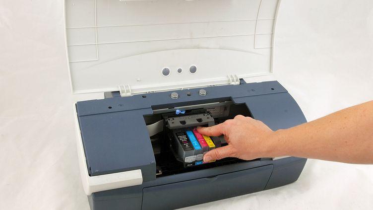 Une personne change les cartouches d'encre de son imprimante, le 13 novembre 2007 en Allemagne. (ARMIN WEIGEL / DPA / AFP)