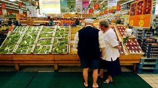 Un couple de retraités devant un étal de fruits et légumes, dans un supermarché de Rots (Calvados), le 17 août 2004. (MYCHELE DANIAU / AFP)
