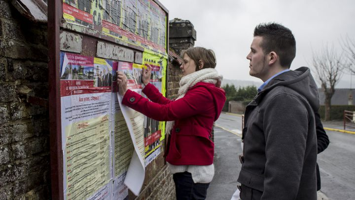 Marie Gallet, candidate suppléante PS pour les élections départementales, colle une affiche dans le canton de Guise (Aisne), le 26 mars 2015. (MATHIEU DEHLINGER / FRANCETV INFO)