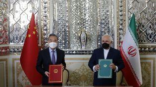 """Le ministre des affaires étrangères iranien,Mohammad Javad Zarifet son homologue Chinois,Wang Yi, lors de la signature d'un""""pacte de coopération stratégique"""", à Téhéran, en Iran, le 27 mars 2021. (FATEMEH BAHRAMI / ANADOLU AGENCY / AFP)"""