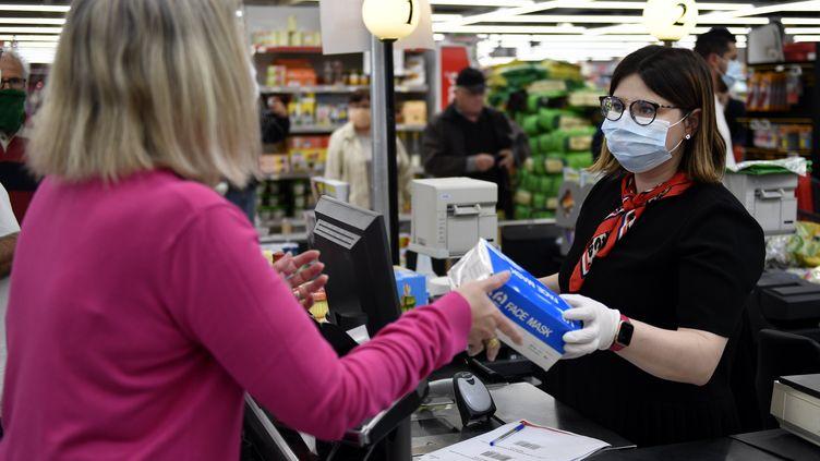 Une hôtesse de caisse du supermarché Intermarché de Ludres (Meurthe-et-Moselle) tend une boîte de masques chirurgicaux qu'une cliente a réservée par internet, le 4 mai 2020. (ALEXANDRE MARCHI / MAXPPP)