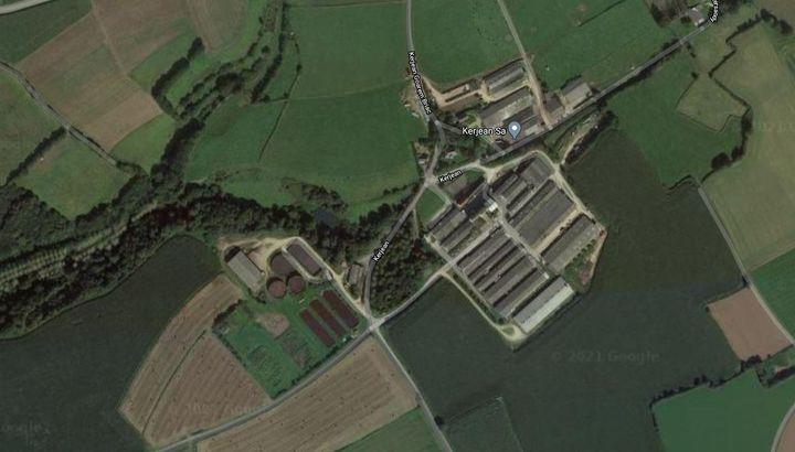 L'exploitation Kerjean SA de Taulé (Finistère), vue du ciel. A droite, les hangars où sont élevés les porcs. A gauche, l'usine de traitement du lisier et ses fosses. Le ruisseau par lequel est arrivé la pollution jusqu'à la Penzé se devine sous les arbres qui partent vers la gauche de l'image. (GOOGLE MAPS)