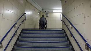 Capture d'écran montrant unhandicapé sur un fauteuil bloqué devant des escaliers de la station de métroCannon Stree,t à Londres. Vidéo publiée le 24 septembre 2014 (THEFREEHELPGUY / YOUTUBE)