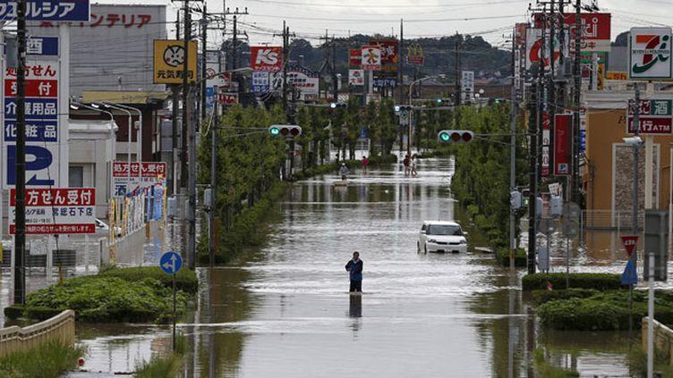 (Un habitant de la ville de Joso, dans la préfecture d'Ibaraki, marche dans sa ville inondée par la rivière Kinugawa. © REUTERS/Issei Kato)