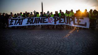 """Des """"gilets jaunes"""" affichent le slogan """"L'Etat ruine le peuple"""", lors d'un blocage place de la Concorde, à Paris, le 17 novembre 2018. (VALENTINA CAMU / HANS LUCAS / AFP)"""