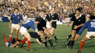 Le Néo-Zélandais John Kirwan (en noir) se fraie un chemin dans la défense française, en finale du Mondial de rugby 1987 à Auckland (Nouvelle-Zélande). (MIKE BRETT / POPPERFOTO / GETTY IMAGES)