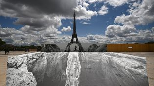 Une fresque de JR installée au Trocadéro, en face de la Tour Eiffel, le 19 mai 2021 (ANNE-CHRISTINE POUJOULAT / AFP)