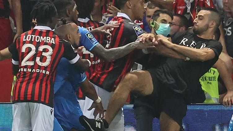 Des joueurs niçois s'interposent alors qu'un de leur supporter descendu sur le terrain tente d'agresser le joueur marseillais Dimitri Payet, le 22 août 2021 à Nice. (VALERY HACHE / AFP)