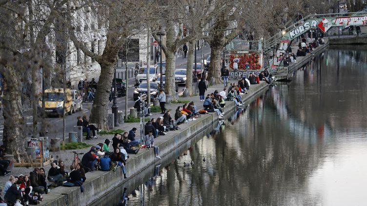 De nombreuses personnes n'ont pas restpectées, dimanche 15 mars 2020, les recommandations de confinement comme ici sur les quais du canal Saint-Martin à Paris. (THOMAS SAMSON / AFP)
