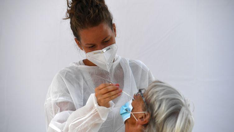 Une soignante réalise un test de dépistage du Covid-19par écouvillonnage à Saint-Nic (Finistère), le 12 août 2020 (photo d'illustration) (FRED TANNEAU / AFP)