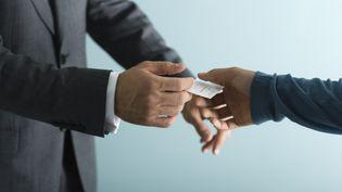 Un homme donne sa carte de visite à un autre homme. (LAURENCE MOUTON / MAXPPP)