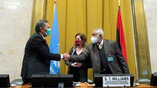 Le chef de la délégation des forces armées arabes libyennes (à gauche) et le chef de la délégation militaire du Gouvernement d'union nationale se serrent la main devant Stephanie Williams, émissaire des Nations unies pour la Libye, le 23 octobre 2020, à Genève (Suisse). (VIOLAINE MARTIN / UNITED NATIONS / AFP)