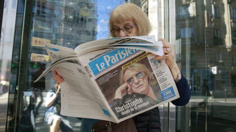 """Une dame lit """"Le Parisien"""" au lendemain de la mort du chanteur Christophe, le 18 avril 2020. (QUENTIN DE GROEVE / HANS LUCAS / AFP)"""