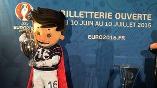 Super Victor, la mascotte de l'Euro 2016, tient une réplique de la coupe durant une présentation de la billetterie mise en place par l'UEFA, le 12 mai 2015. (GERD ROTH / DPA / AFP)