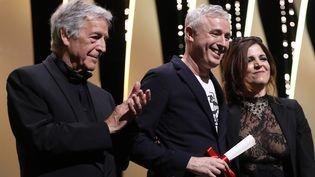 """Le réalisateur français Robin Campillo (au centre), récompensé par le Grand prix pour son film """"120 battements par minute"""" au 70e festival de Cannes, le 28 mai 2017. (VALERY HACHE / AFP)"""