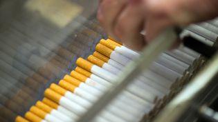 Dans une usine de cigarettes, un employé contrôle à Dresde en Allemagne le 22 janvier 2014. (ARNO BURGI / ZB)