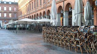 Des piles de chaises devant un restaurant fermé place du Capitole à Toulouse (Haute-Garonne). Photo d'illustration. (ERIC CABANIS / AFP)