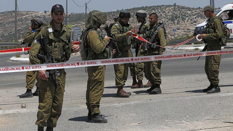Des soldats israéliens montent la garde le 15 août 2015 en Cisjordanie après une attaque à l'arme blanche contre l'un d'entre eux. (AHMAD GHARABLI / AFP)