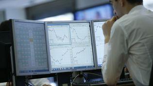 Les différents cours de la Bourse visualisés par un opérateur sur des écrans, à Paris. (THOMAS SAMSON / AFP)