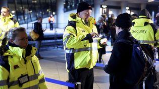 Le personnel de sécurité effectue des contrôles àl'aéroport de Kastrup, prèsde Copenhague (Danemark), pour les voyageurs se rendant en Suède. (BJORN LINDGREN / TT NEWS AGENCY / AFP)