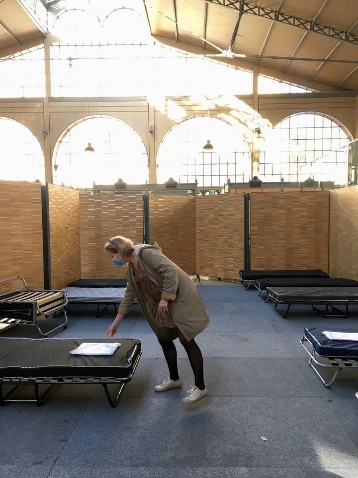 Personnel de l'association Aurore déposant des kits de draps sur des lits pour les personnes souhaitant se reposer lors de l'accueil de jour, à Paris, le 12 novembre 2020. (GUILLEMETTE JEANNOT / FRANCEINFO)