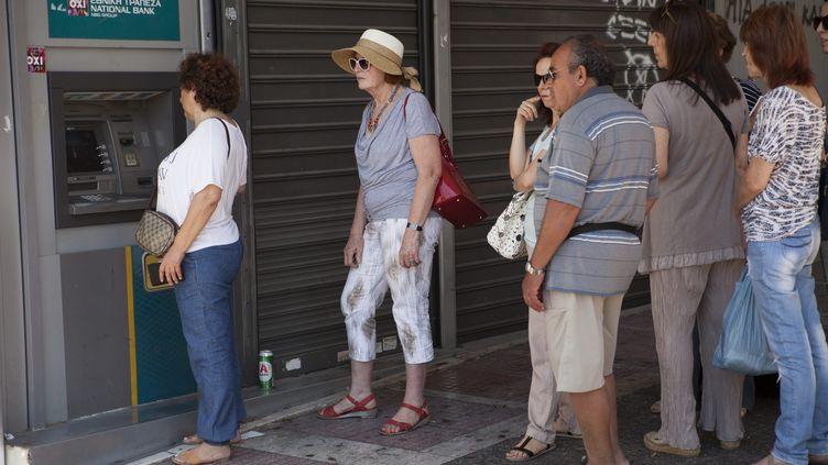 Des Grecs font la queue devant un distributeur, le 6 juillet 2015. (ROBERT GEISS / PICTURE ALLIANCE / AFP)
