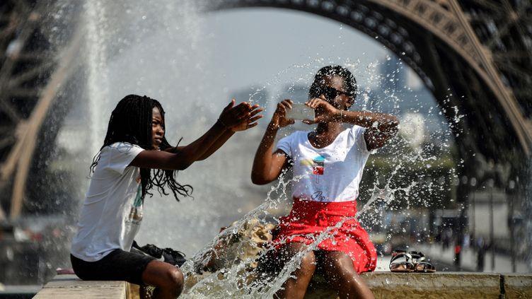 Deux personnes se rafraîchissent dans une fontaine au Trocadéro, à Paris, le 25 juillet 2018, lors d'une forte vague de chaleur. (BERTRAND GUAY / AFP)