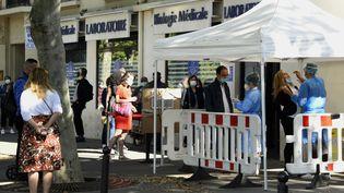 Des gens font la queue devant un laboratoire médical à Paris pour être dépisté contre coronavirus, le 18 juillet 2020. (BERTRAND GUAY / AFP)