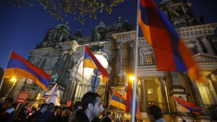 Des Arméniens brandissent leur drapeau lors d'une marche commémorant le centenaire du génocide arménien, le 23 avril 2015 à Berlin (Allemagne). (FABRIZIO BENSCH / REUTERS)