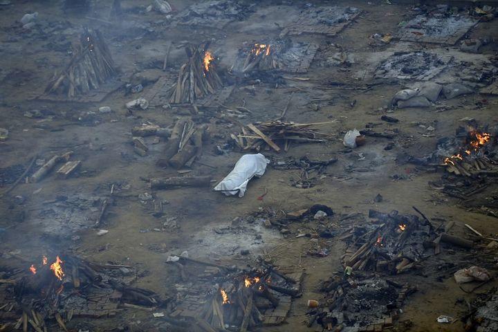 Un corps est étendu au sol près de bûchers funéraires de victimes du Covid-19 à New Delhi (Inde), le 26 avril 2021. (MONEY SHARMA / AFP)