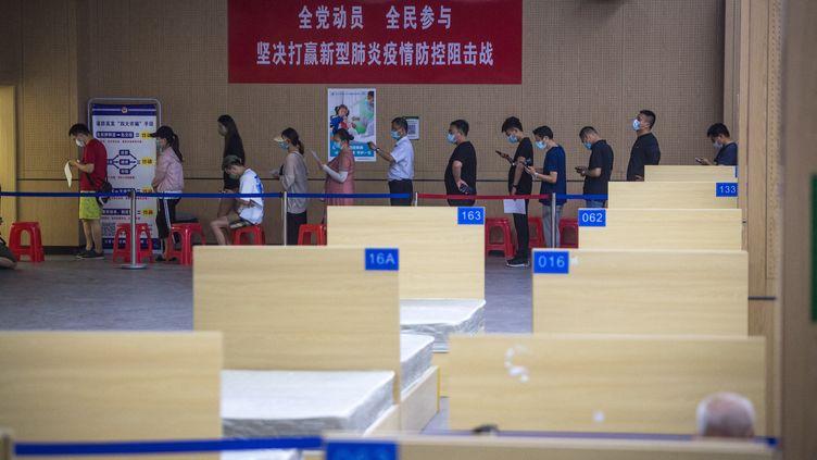 Des personnes font la queue pour être vaccinées à Wuhan, en Chine, le 9 juin 2021. (XIAO YIJIU / XINHUA / AFP)