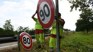 Echange de panneaux 80km/h et 90km/h sur une route à Wittenheim (Haut-Rhin). (SEBASTIEN BOZON / AFP)
