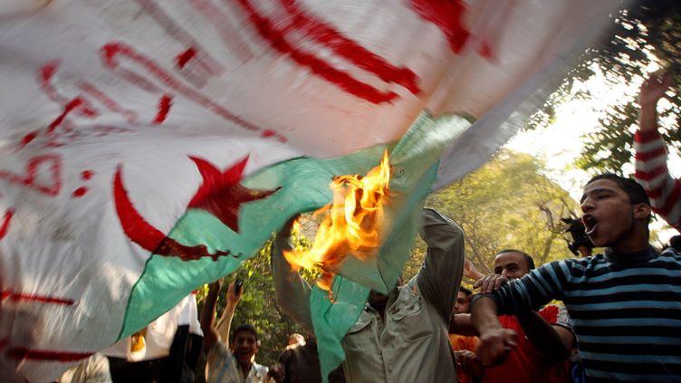 Des supporters égyptiens brûlent un drapeau algérien près de l'ambassade d'Algérie au Caire le 20 novembre 2009, pour protester contre la qualification de ce pays pour la Coupe du monde 2010. (CRIS BOURONCLE / AFP)