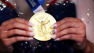 La gymnaste américaine Sunisa Lee présente sa médaille d'or après sa victoire au concours complet individuel aux Jeux de Tokyo, le 29 août 2021. (LAURENCE GRIFFITHS / GETTY IMAGES ASIAPAC)