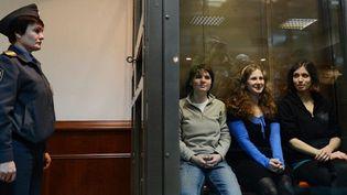 Les trois Pussy Riot dans une cage en verre mercredi matin à Moscou  (NATALIA KOLESNIKOVA / AFP)