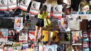 Le Off d'Avignon : une jeune femme installe ses affiches sur un mur de la ville, le 4 juillet 2018. (PATRICK ROUX / MAXPPP)