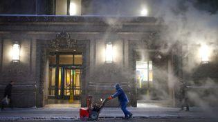 Un employé municipal pousse un chasse-neige, le 26 janvier 2015, à New York, en plein blizzard. (CARLO ALLEGRI / REUTERS)
