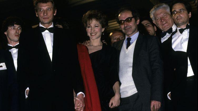 """Johnny Hallyday, Nathalie Baye et Jean-Luc Godard (de gauche à droite) au festival de Cannes pour la présentation film """"Dètective"""", en mai 1985. (JEAN-LOUIS URLI / GAMMA-RAPHO)"""